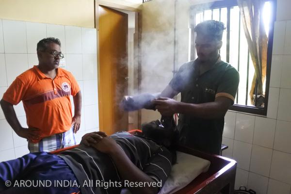 インドのアーユルヴェーダ病院男性セラピストに男性生徒がトリートメントを習っているところ