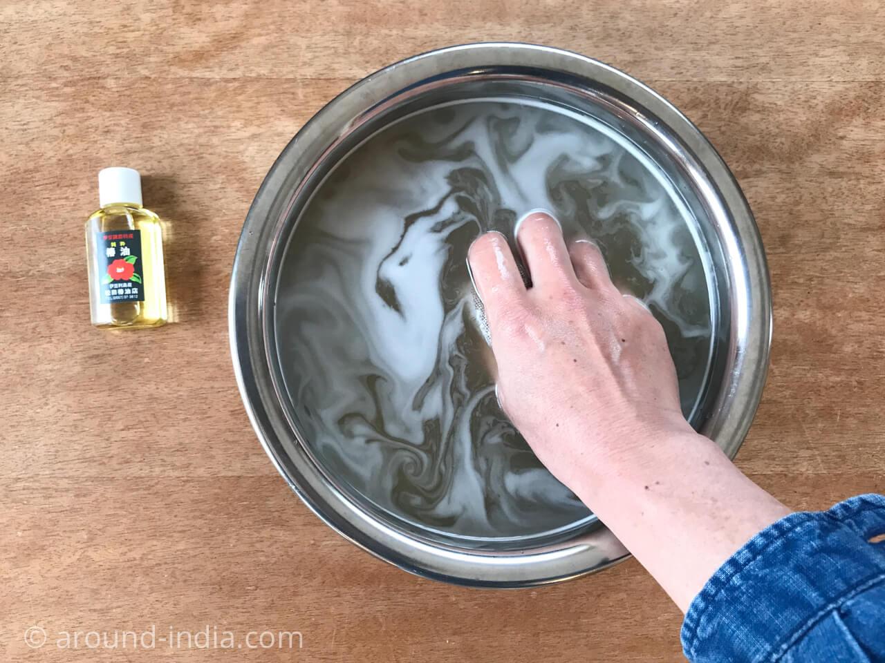 髪洗い粉(椿油カス)を湯の中で揉みます