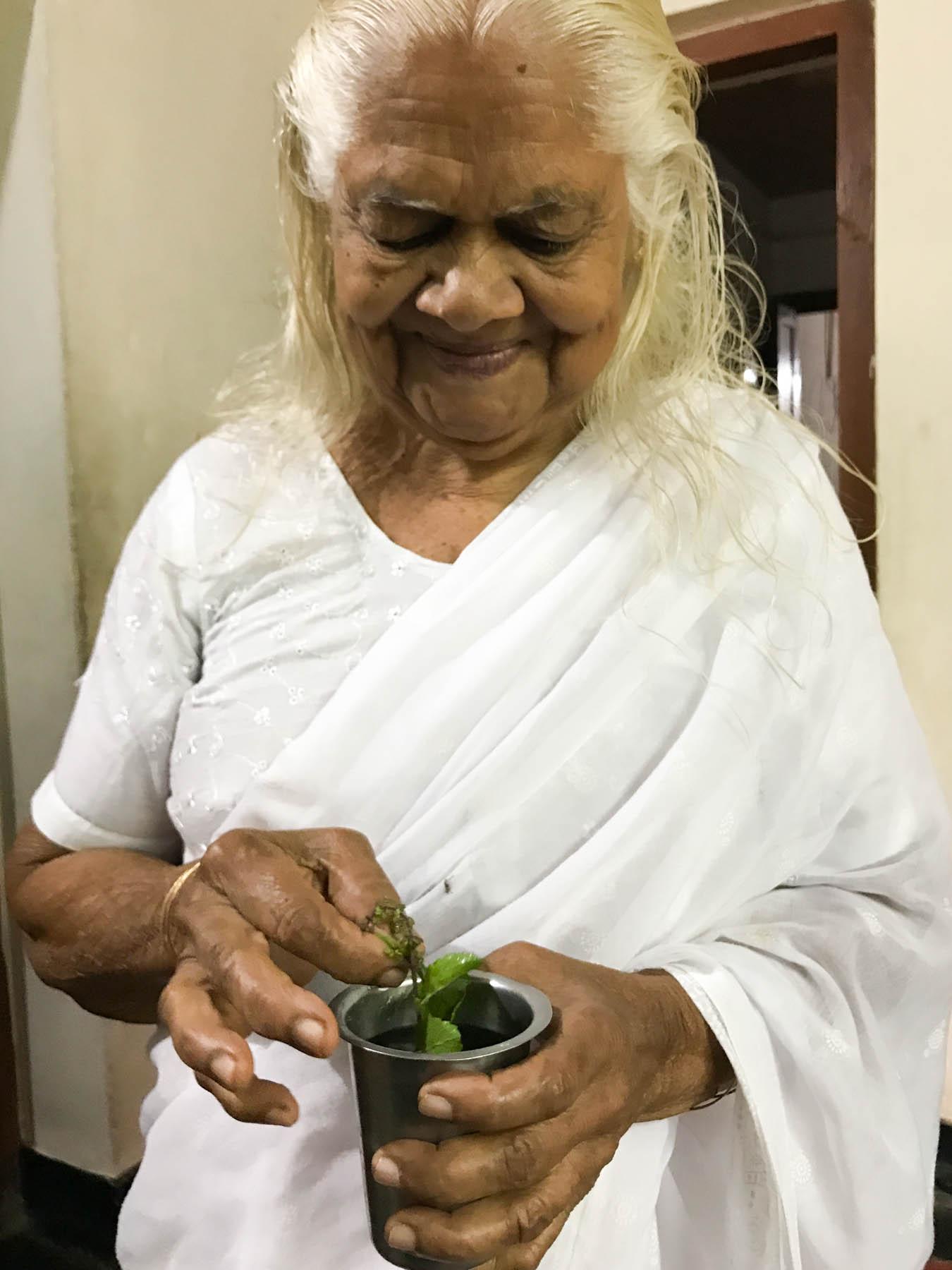 ケララの村のお宅で、トゥルシー水を日課にするおばあさん