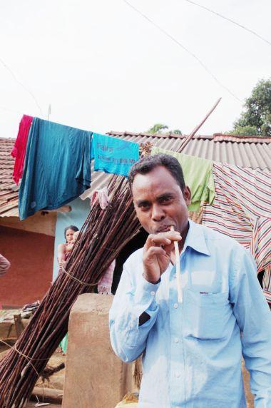 朝ニームの枝歯ブラシで歯磨きするオリッサ州の少数民族の男性