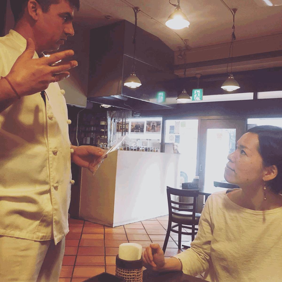 ダクシン東日本橋店でシェフからレメディについて話を聞くAROUND INDIAの田村ゆみ
