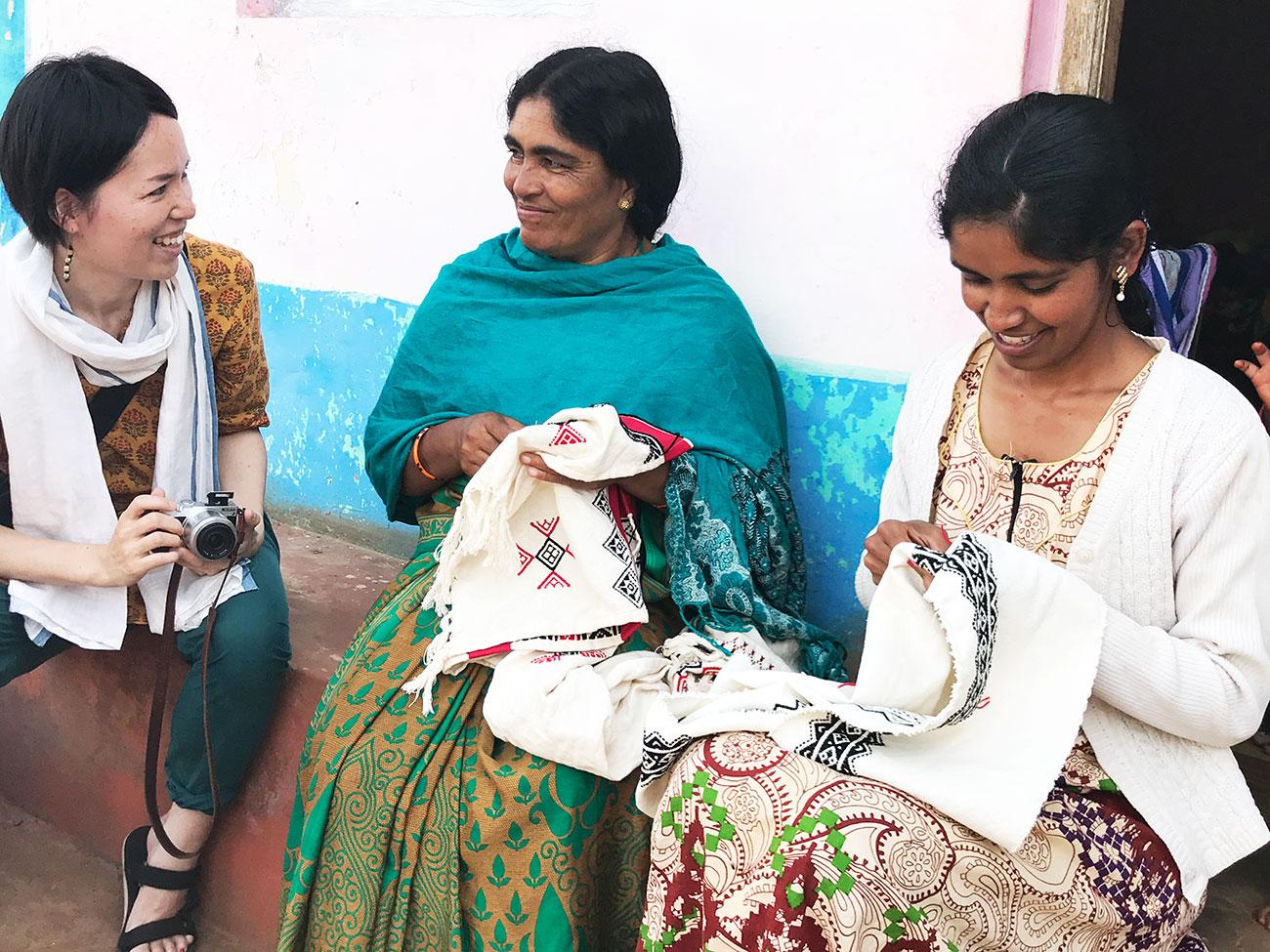 家の前に腰掛けて刺繍するトダ族の女性たち
