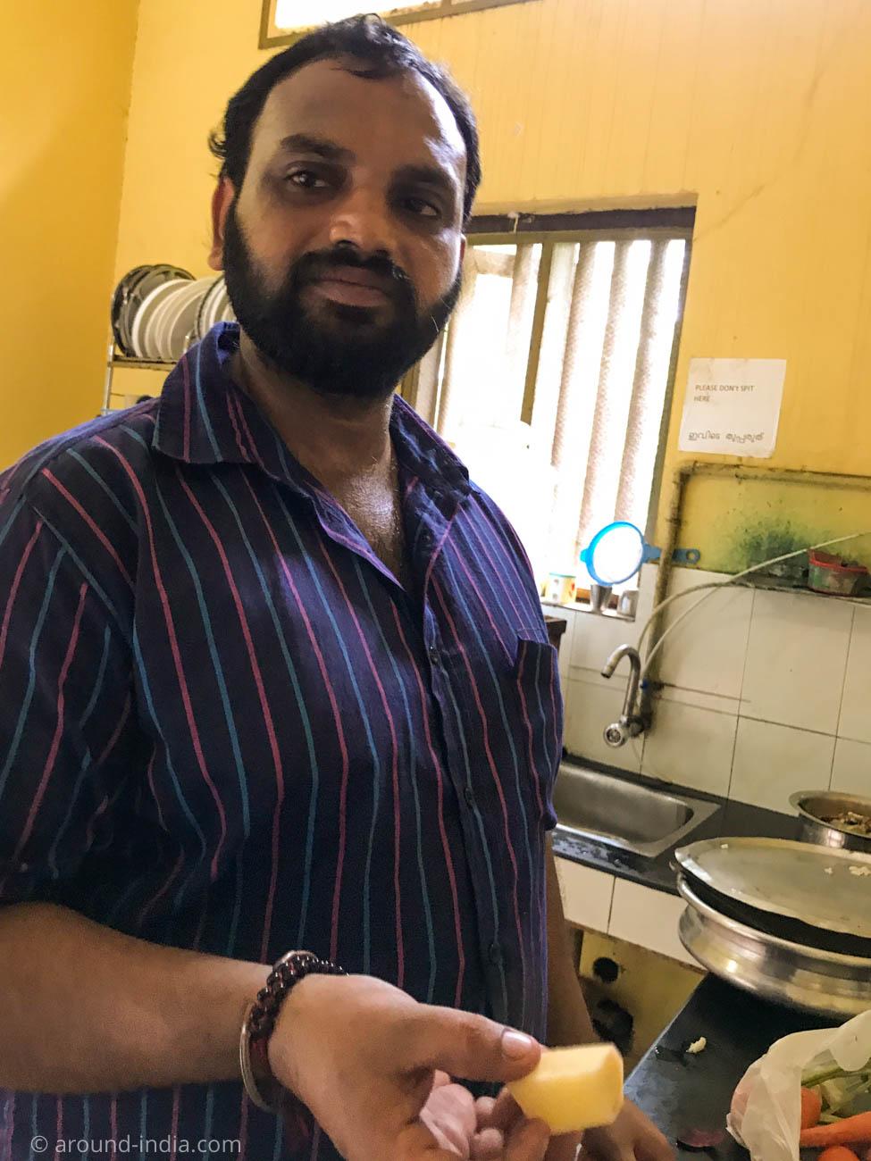 PVAアーユルヴェーダ病院のキッチンで、ランチ用サンバルのバナナを見せてくれるシェフのラジェシ
