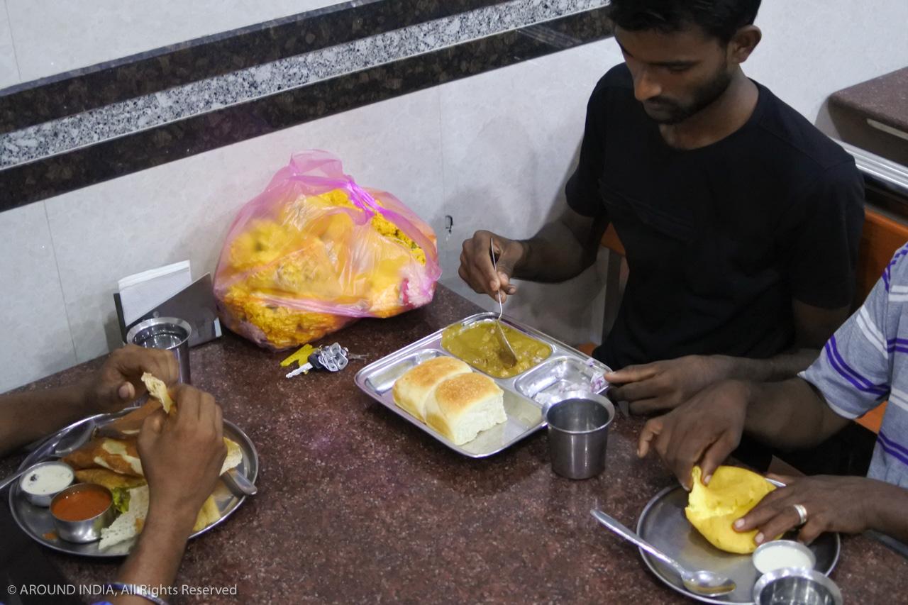インド・ゴアSheetal Pure Veg Restaurantでパンを食べる人々
