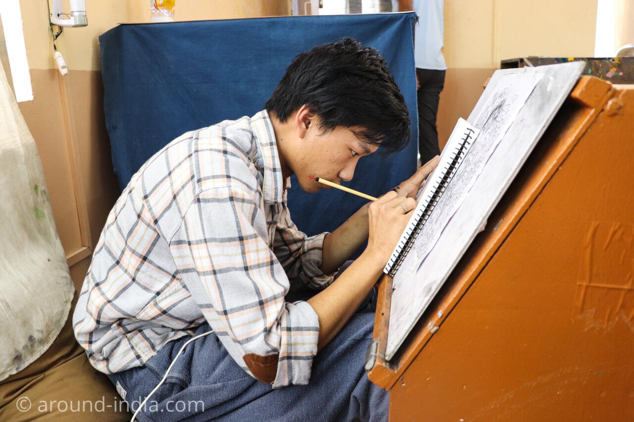 ダラムサラのノルブリンカチベット芸術 真剣なまなざしでタンカに取り組む青年