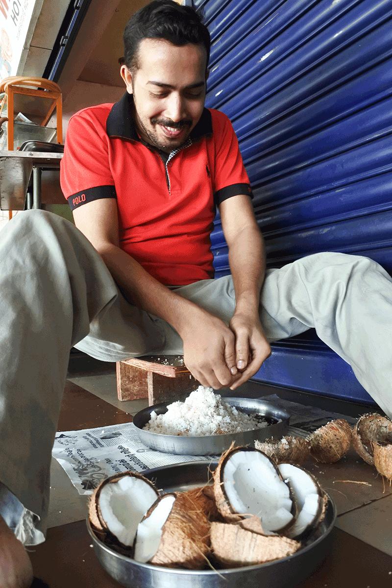 ケララで食堂用のココナッツを削るお兄さん